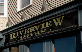 Image shows the wooden facade sign for the Riverview Tavern in Roscoe Village Chicago, IL