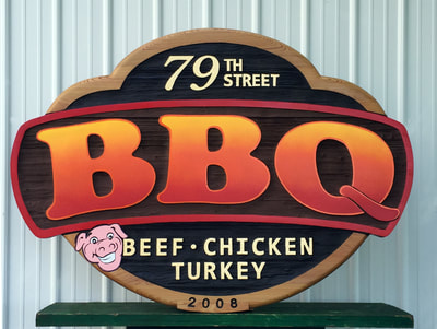 Image shows sandblasted Cypress wall sign for 79th Street BBQ in Chicago. Made in our Elkhorn Wisconsin studio, Signs Madison