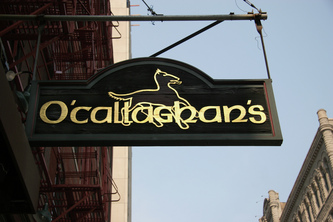 Image shows wooden hanging blade sign for O'Callaghan's Chicago,IL