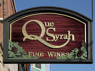 Image of the sandblasted HDU blade sign for the Que Syrah Wine Store in Old Town Chicago, IL